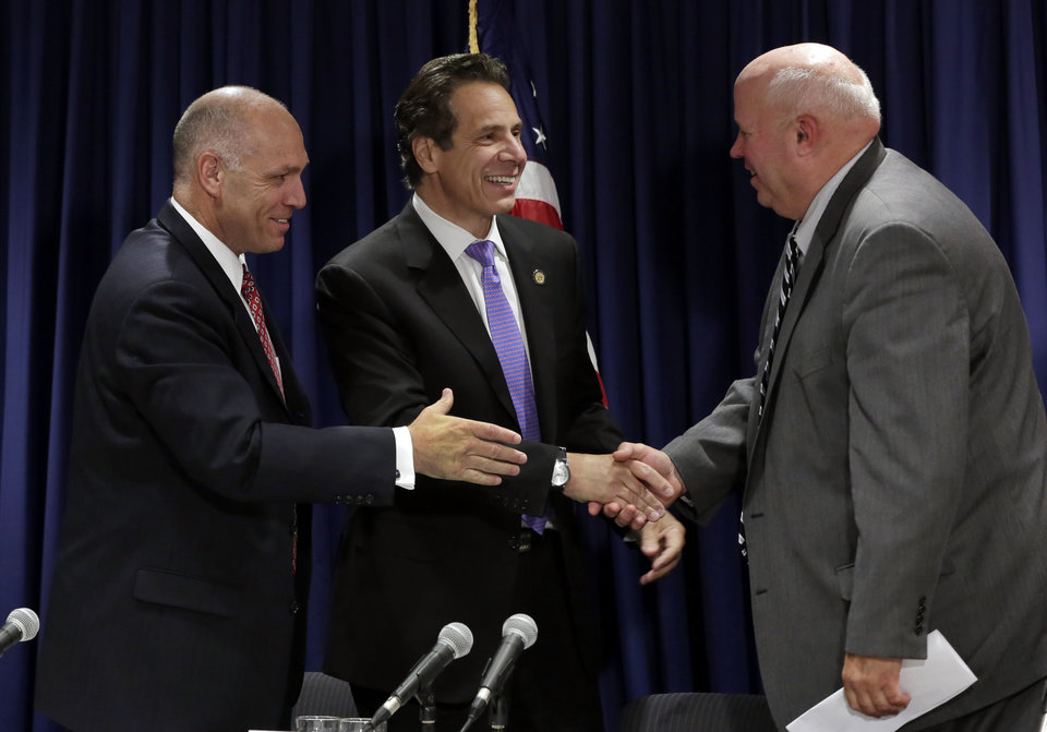 Photo - Anthony Simon, general chairman of the United Transportation Union, left,  Metropolitan Transportation Authority Chairman Thomas Prendergast, right, and  New York Gov. Andrew Cuomo share a collective hand shake after a tentative labor agreement for the Long Island Rail Road was reached, at the New York office of Gov. Cuomo, Thursday, July 17, 2014. Eight unions representing 5,400 LIRR workers had threatened to strike this weekend unless an agreement was reached. The workers had been seeking a new deal since 2010. (AP Photo/Richard Drew)