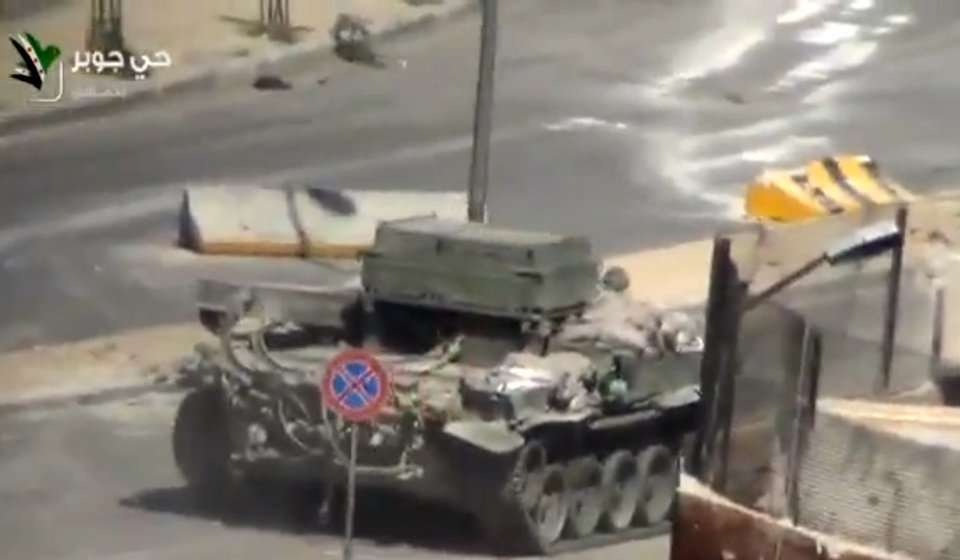 Photo - This image taken from video obtained from Ugarit, which has been authenticated based on its contents and other AP reporting, shows a Syrian Army tank in the streets of the Jobar district of Damascus, Syria, Friday, April 26, 2013. On the streets of Damascus, the two-year old conflict dragged on Friday, with government troops pushing into two northern neighborhoods, triggering heavy fighting with rebels as they tried to advance under air and artillery support, activists said. The Britain-based Syrian Observatory for Human Rights said the fighting between rebels and soldiers backed by pro-government militiamen was concentrated in the Jobar and Barzeh areas.(AP Photo/Ugarit via AP video)