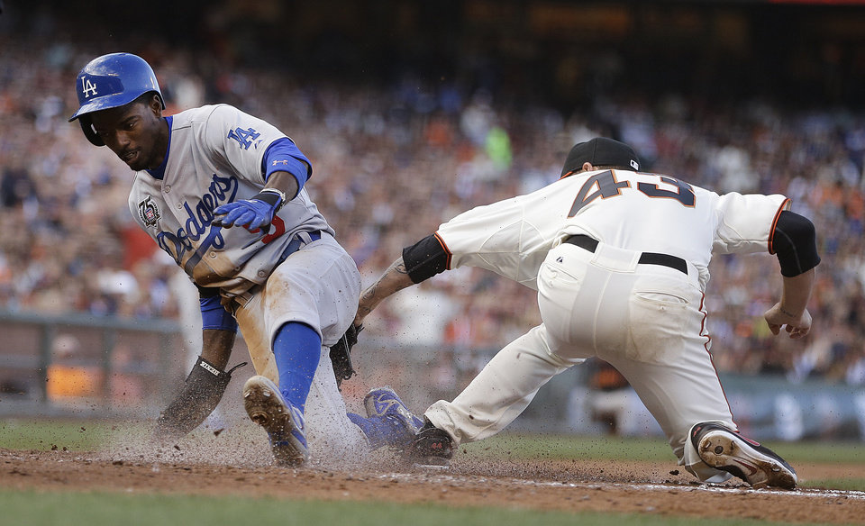 Photo - Los Angeles Dodgers' Dee Gordon, left, scores past San Francisco Giants pitcher Jake Peavy in the fifth inning of a baseball game Sunday, July 27, 2014, in San Francisco. (AP Photo/Ben Margot)