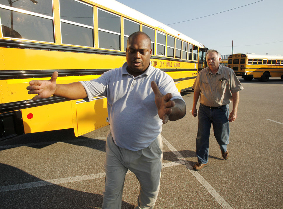 Photo - Trainer Bruce Luster briefs Mark English on bus driving techniques.  Photo By Paul Hellstern, The Oklahoman