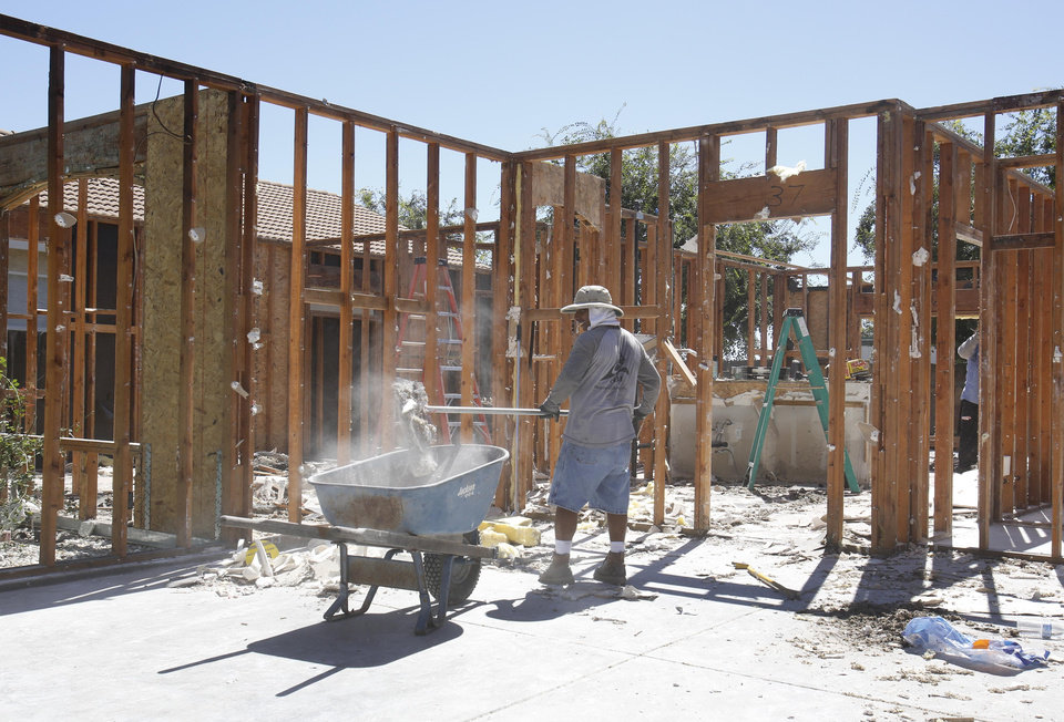 A worker clears debris from a home destroyed by a suspicious fire in Yuba City, Calif., Thursday, Aug. 29, 2013. Sutter County District Attorney Carl Adams was one of several suitors of the homes's occupant, Sarah Garibay, 32, who said she had a brief affair with the district attorney.  Garibay told investigators he was one of three lovers who had recently expressed jealousy or anger toward her but she told the Marysville Appeal-Democrat that she does not believe he is in involved in the fire that destroyed the home in July. (AP Photo/Rich Pedroncelli)