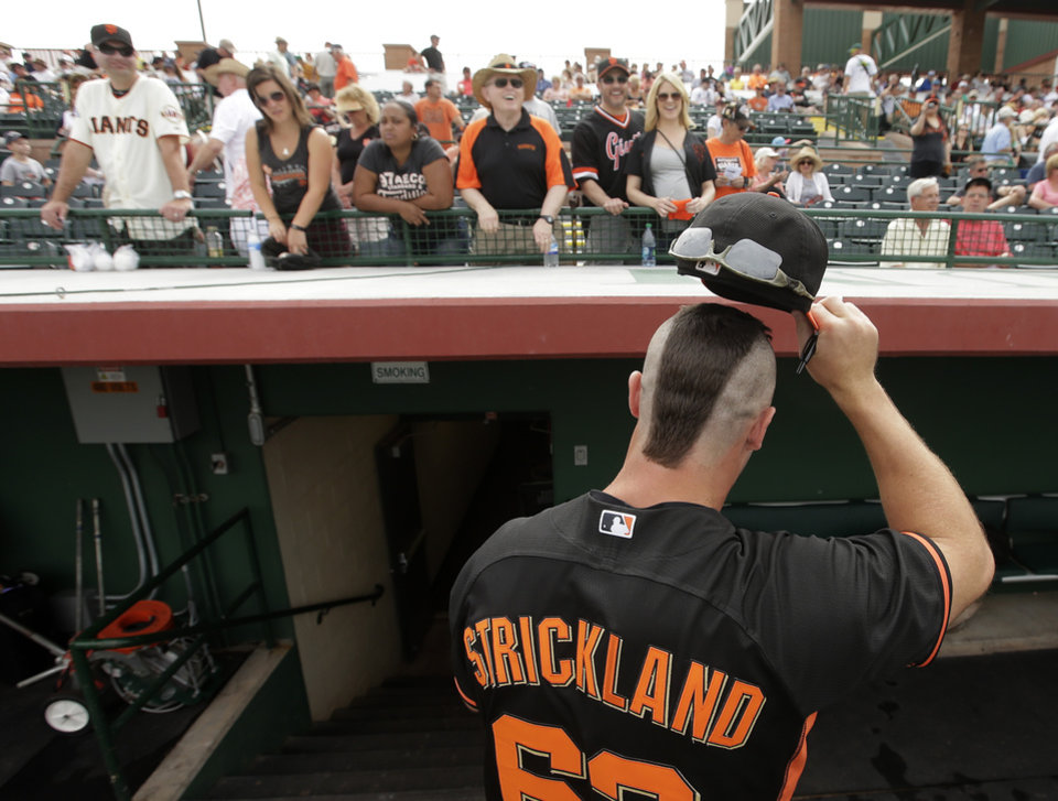 Photo - San Francisco Giants relief pitcher Hunter Strickland shows off his haircut to fans before a spring training baseball game against the Cincinnati Reds in Scottsdale, Ariz., Thursday, March 6, 2014. (AP Photo/Chris Carlson)