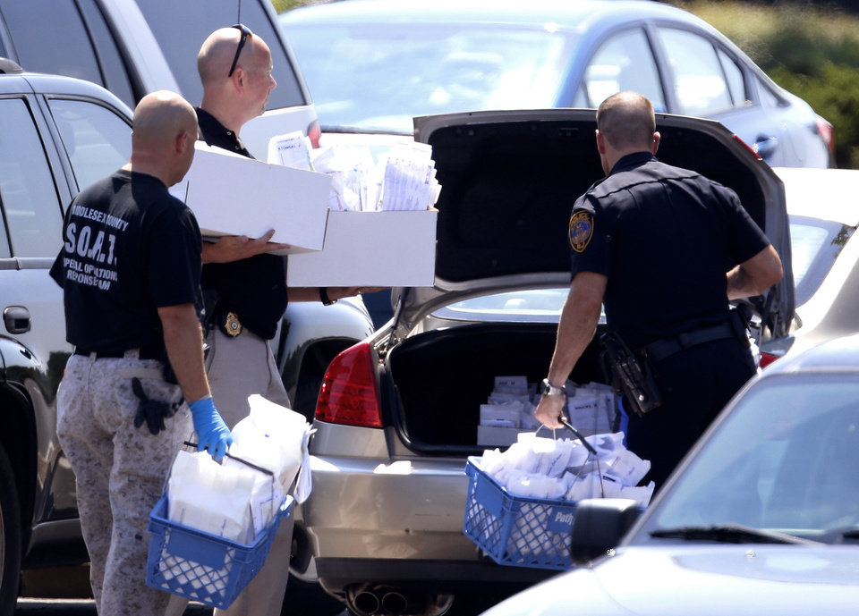 Photo -   Officials remove evidence from a Pathmark grocery store where three people died in an early morning shooting in Old Bridge, N.J., Friday, Aug. 31, 2012. Officials say a supermarket employee killed two people at the store early Friday and then fatally shot himself. Authorities say he opened fire on employees he saw when he walked into the Pathmark store. The store's front windows were shattered by gunfire. The motive is being investigated. (AP Photo/Julio Cortez)