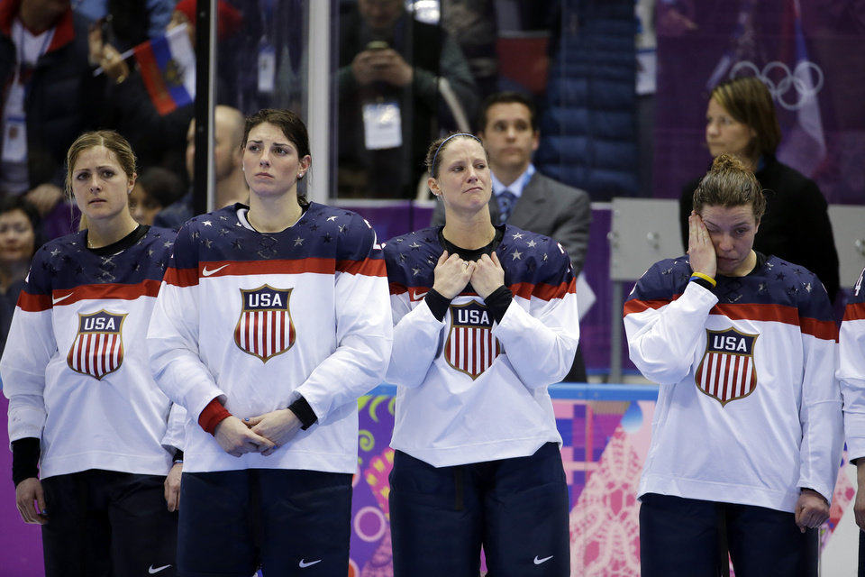 Photo - Team USA awaits their silver medals after losing 3-2 in overtime to Canada in the gold medal women's ice hockey game at the 2014 Winter Olympics, Wednesday, Feb. 19, 2014, in Sochi, Russia. (AP Photo/David Goldman)