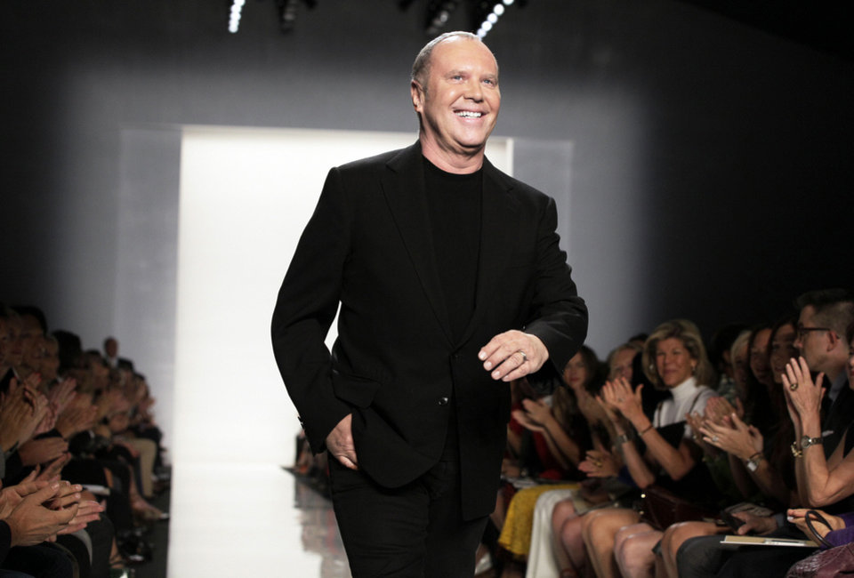 Photo - Designer Michael Kors acknowledges applause after his Spring 2013 collection was modeled during Fashion Week in New York. AP Photo
