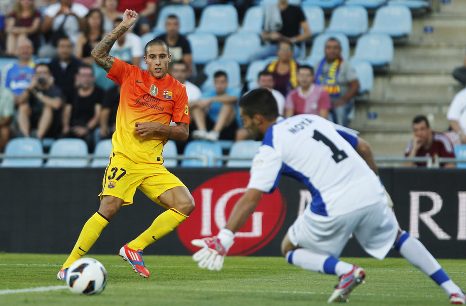 Photo -   FC Barcelona's Tello, left, tries to score facing Getafe's goalkeeper Miguel Angel Moya during a Spanish La Liga soccer match at the Coliseum Alfonso Perez stadium in Getafe, near Madrid, Spain, Saturday, Sept. 15, 2012. (AP Photo/Andres Kudacki)