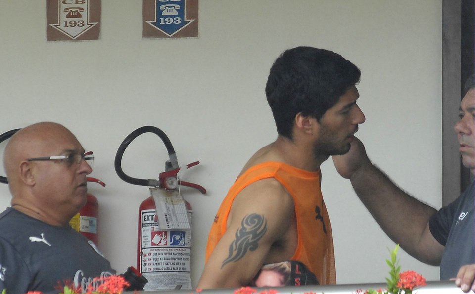 Photo - Uruguay striker Luis Suarez, center, talks with Uruguayan team members at the Serhs Hotel in Natal, Brazil, Thursday, June 26, 2014. FIFA banned Suarez from all football activities for four months on Thursday for biting an opponent at the World Cup, a punishment that rules him out of the rest of the tournament. (AP Photo/Vlademir Alexandre)