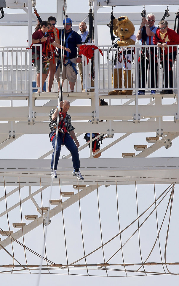 Photo - Barry Switzer rides the new SandRidge Sky Zip that spans the Oklahoma River in the Boathouse District in Oklahoma City, Thursday May, 22, 2014. Photo by Bryan Terry, The Oklahoman