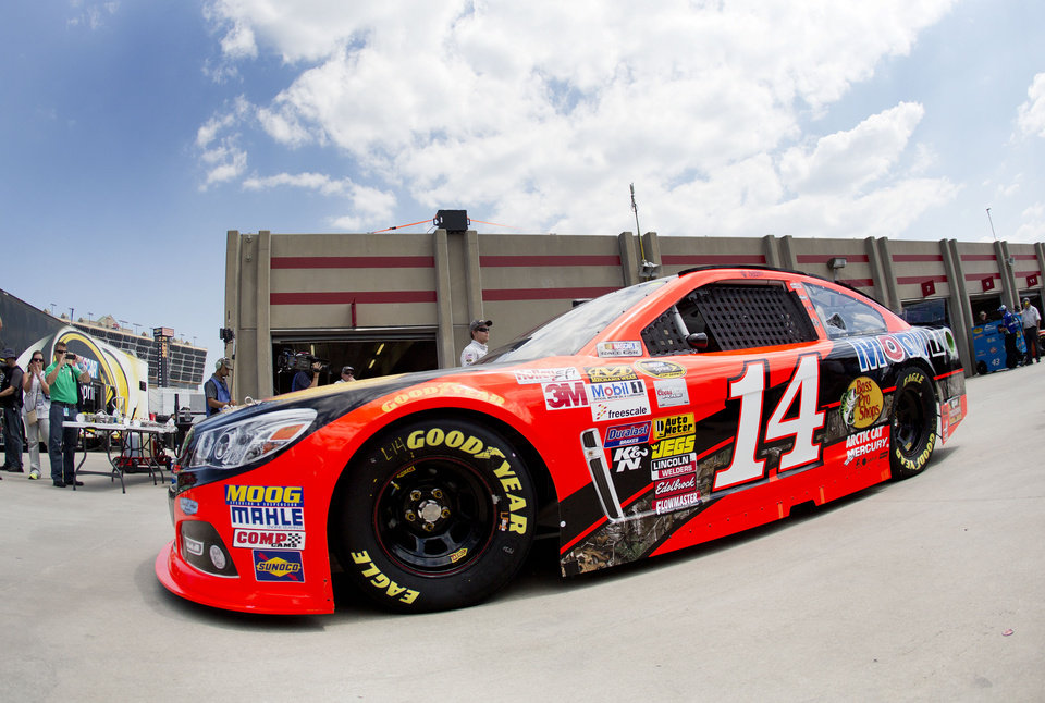Photo - NASCAR driver Tony Stewart leaves his garage during practice for Sunday's auto race at Atlanta Motor Speedway in Hampton, Ga., Friday, Aug. 29, 2014. Sunday's race will be his first since his car struck and killed a fellow driver during a sprint race in New York three weeks ago. (AP Photo/John Bazemore)
