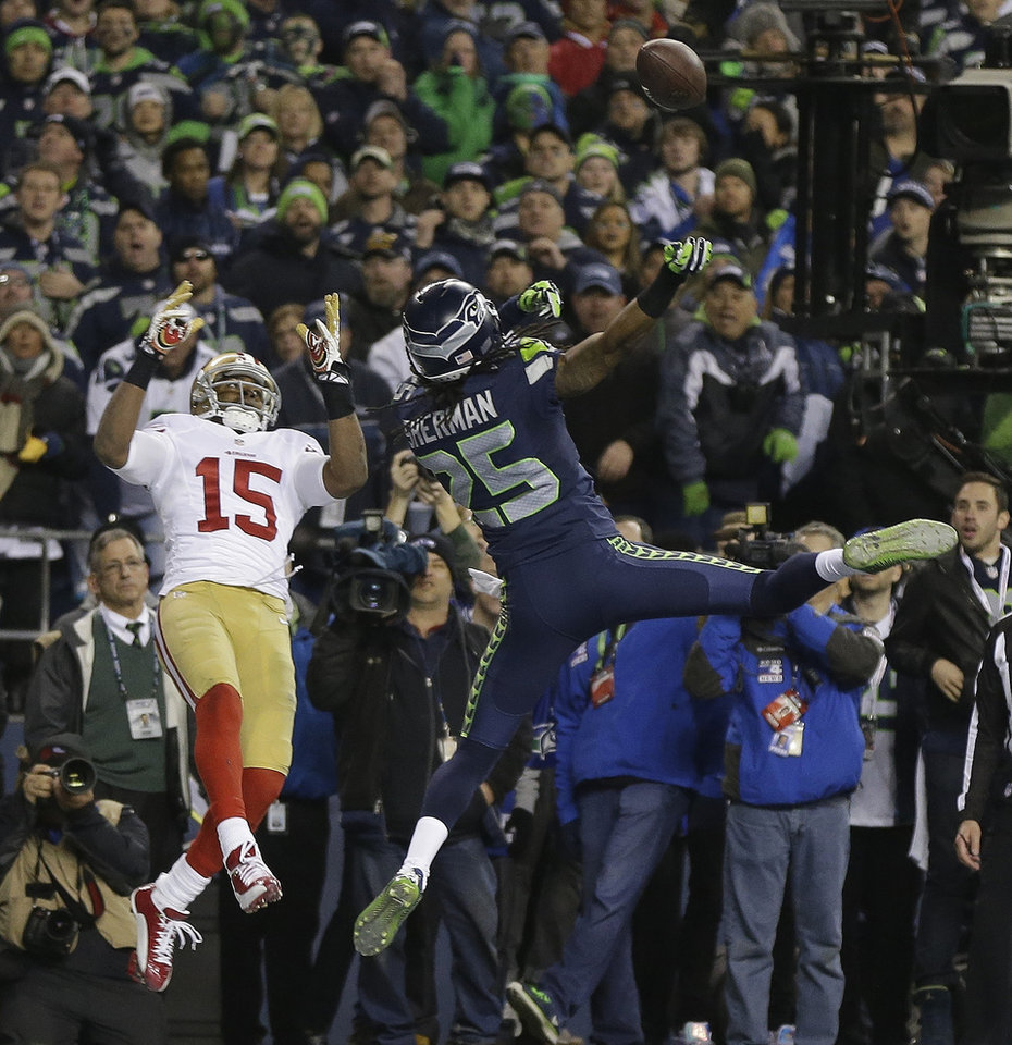 Photo - Seattle Seahawks' Richard Sherman tips a pass intended for San Francisco 49ers' Michael Crabtree (15) in the final seconds of the second half of the NFL football NFC Championship game Sunday, Jan. 19, 2014, in Seattle. Malcolm Smith intercepted the tipped pass. The Seahawks won 23-17 to advance to Super Bowl XLVIII. (AP Photo/Marcio Jose Sanchez)