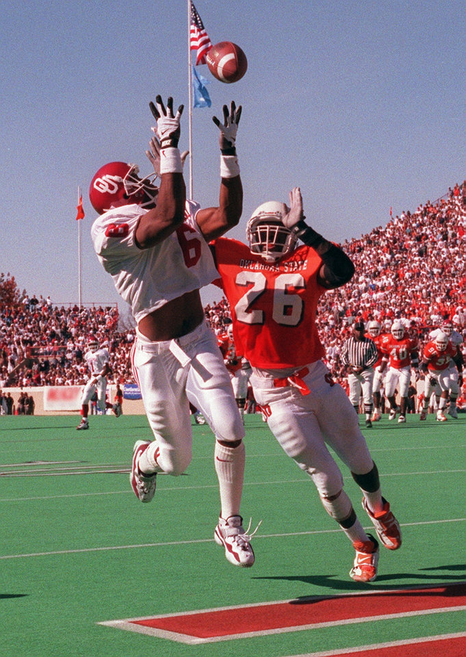 Photo - OU's Michael McDaniel makes a touchdown catch from Eric Moore (in background) as OSU's Jitu Criddle defends during the Bedlam college football game on Nov. 9, 1996. Photo by Doug Hoke, The Oklahoman