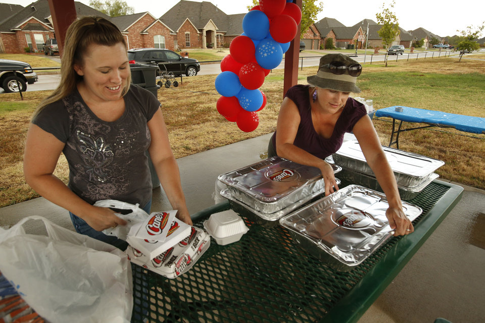 Neighbors Adrian Gates and Kristen Sharp set up food for a potluck dinner Tuesday at Summit Lake Park as part of this year's National Night Out celebration. PHOTO BY STEVE SISNEY, THE OKLAHOMAN