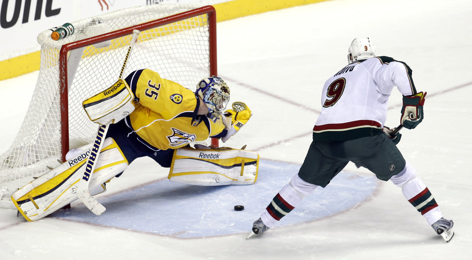 Minnesota Wild center Mikko Koivu (9), of Finland, scores against Nashville Predators goalie Pekka Rinne (35), of Finland, during a shootout at an NHL hockey game on Saturday, March 9, 2013, in Nashville, Tenn. The Wild won the shootout to win the game 2-1. (AP Photo/Mark Humphrey)