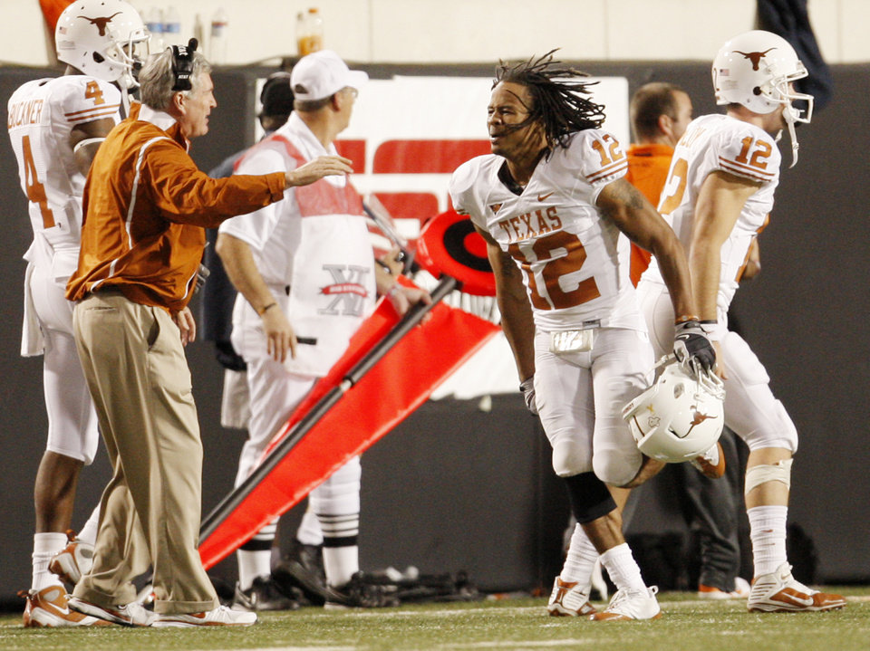 Photo - Texas' Earl Thomas (12) runs the sideline celebrating his interception for a touchdown during the college football game between the Oklahoma State University Cowboys (OSU) and the University of Texas Longhorns (UT) at Boone Pickens Stadium in Stillwater, Okla., Saturday, Oct. 31, 2009. Photo by Doug Hoke, The Oklahoman