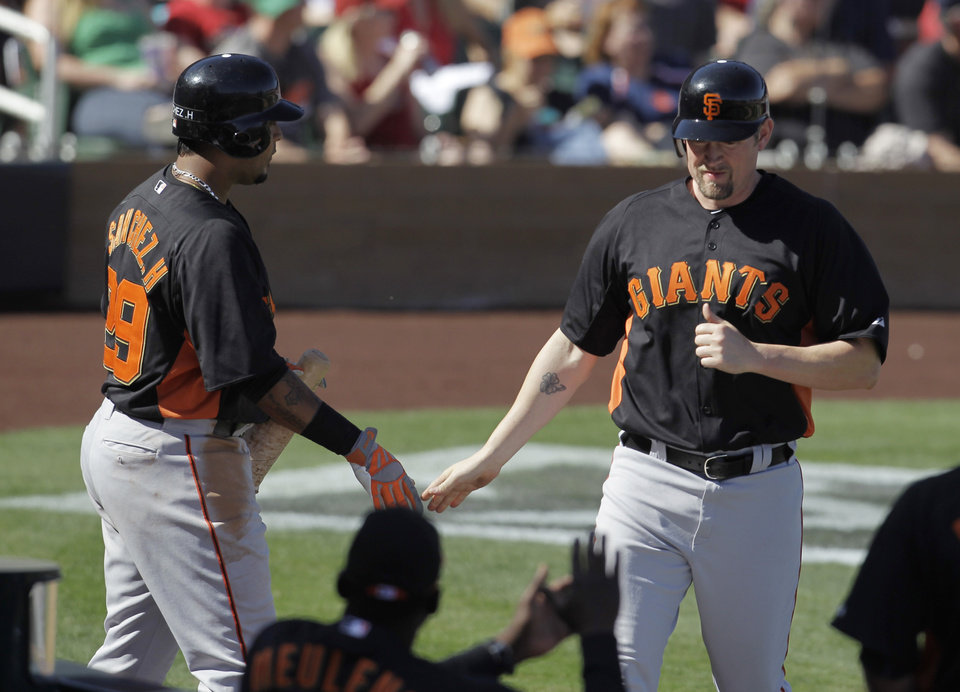 Photo -   San Francisco Giants' Aubrey Huff, right, is congratulated by Hector Sanchez after scoring during the third inning of a spring training baseball game against the Arizona Diamondbacks, Sunday, March 4, 2012, in Scottsdale, Ariz. (AP Photo/Darron Cummings)