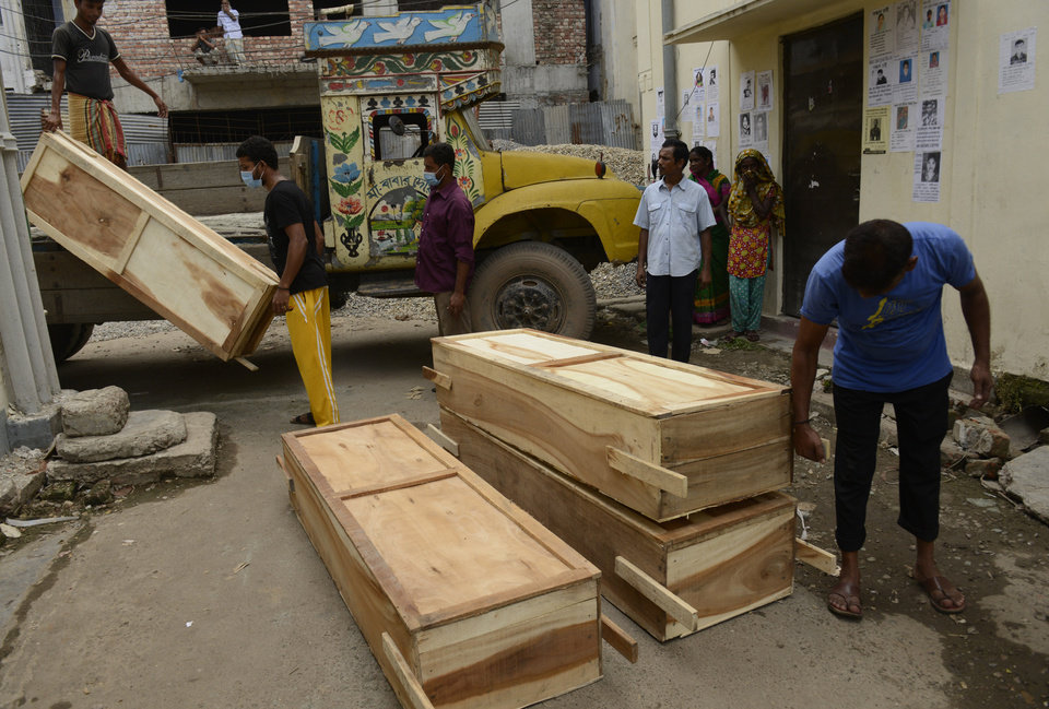 Photo - Workers off-load coffins at a morgue on Wednesday May 1, 2013 in Dhaka, Bangladesh where a building housing garment factories that collapsed last week in the country's worst industrial disaster, left at least 402 people and injuring 2,500.(AP Photo/Ismail Ferdous)