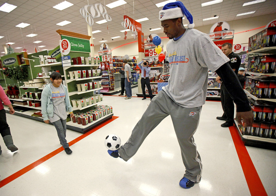 Photo - Serge Ibaka with the Oklahoma City Thunder kicks a soccer ball with Bianka Tobias, 14, during a shopping spree with the Sunbeam Family Services Grandparents Raising Grandkids program and the Thunder at a Target store in Oklahoma City, Thursday, December 16, 2010.  Photo by Bryan Terry, The Oklahoman