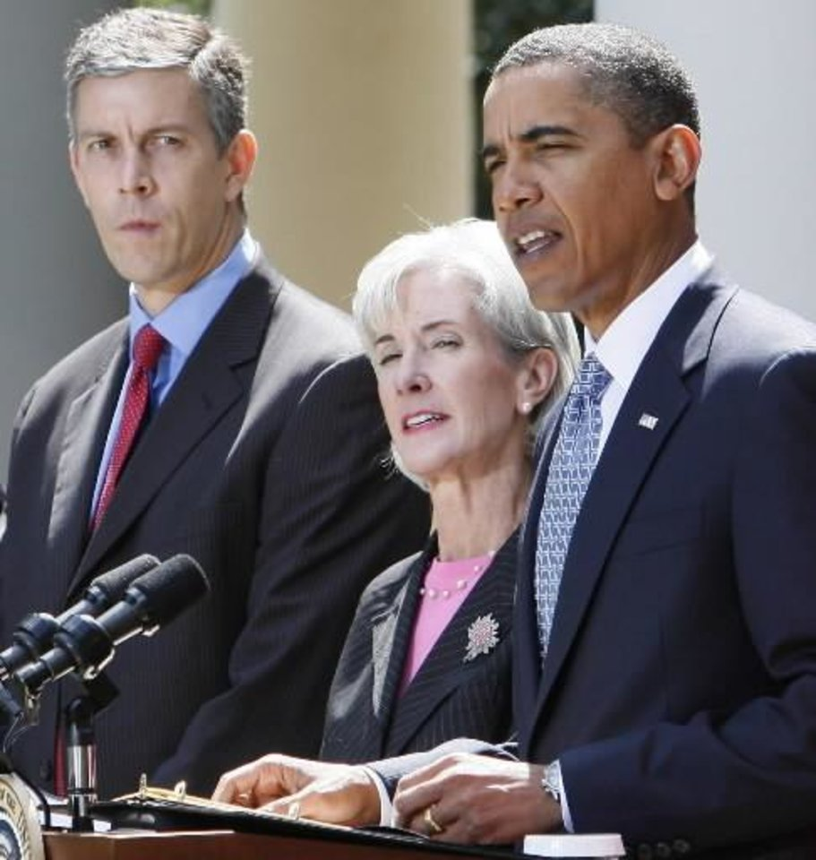 Photo - President Barack  Obama stands with Education Secretary Arne Duncan, left, and  Health and Human Services Secretary Kathleen Sebelius, center, as he speaks about the H1N1 swine flu virus in the Rose Garden of the White House in Washington, Tuesday, Sept. 1, 2009. (AP Photo/Charles Dharapak)