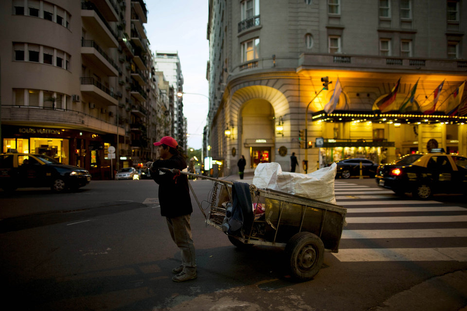 In this Sept. 26, 2012 photo, a cardboard picker stands in front of a Louis Vuitton store, left, and the Alvear Hotel, right, along Alvear Avenue in the Recoleta neighborhood in Buenos Aires, Argentina. The world's most luxurious designer brands are abandoning Argentina rather than complying with tight new government economic restrictions, leaving empty shelves and storefronts along the capital's elegant Alvear Avenue, where tourists once flocked to see the latest in fashion. (AP Photo/Natacha Pisarenko)