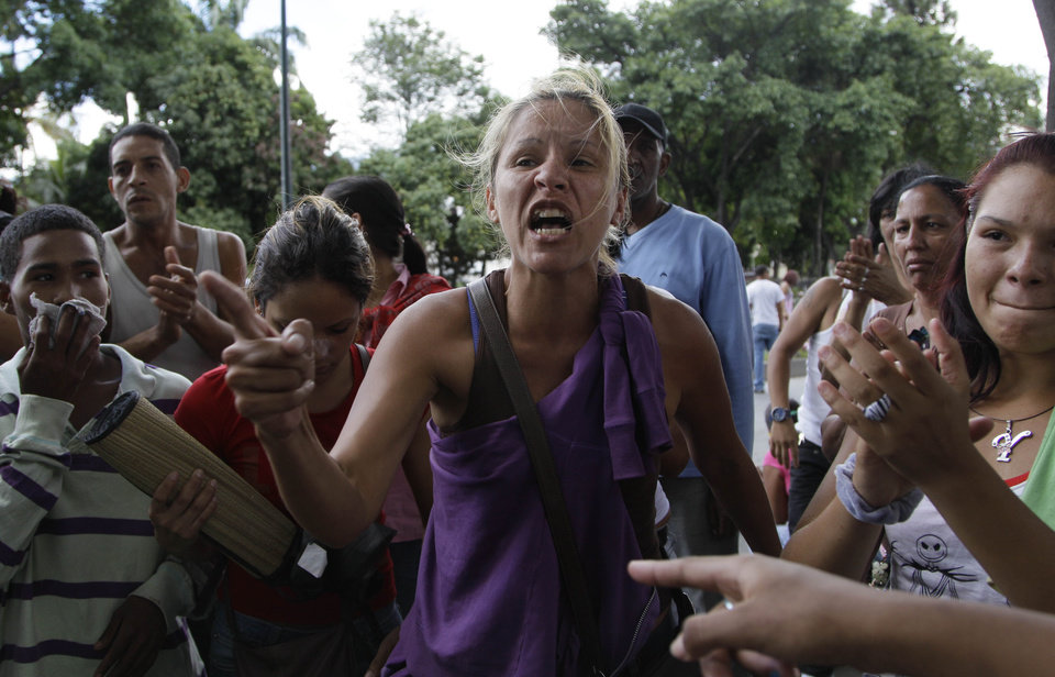 Photo -   Relatives of inmates protest against measures taken by authorities to control a riot at the La Planta prison outside the jail in Caracas, Venezuela, Thursday, May 17, 2012. Gunfire erupted on Thursday inside the prison where armed inmates have prevented security forces from retaking control for nearly three weeks. (AP Photo/Ariana Cubillos)