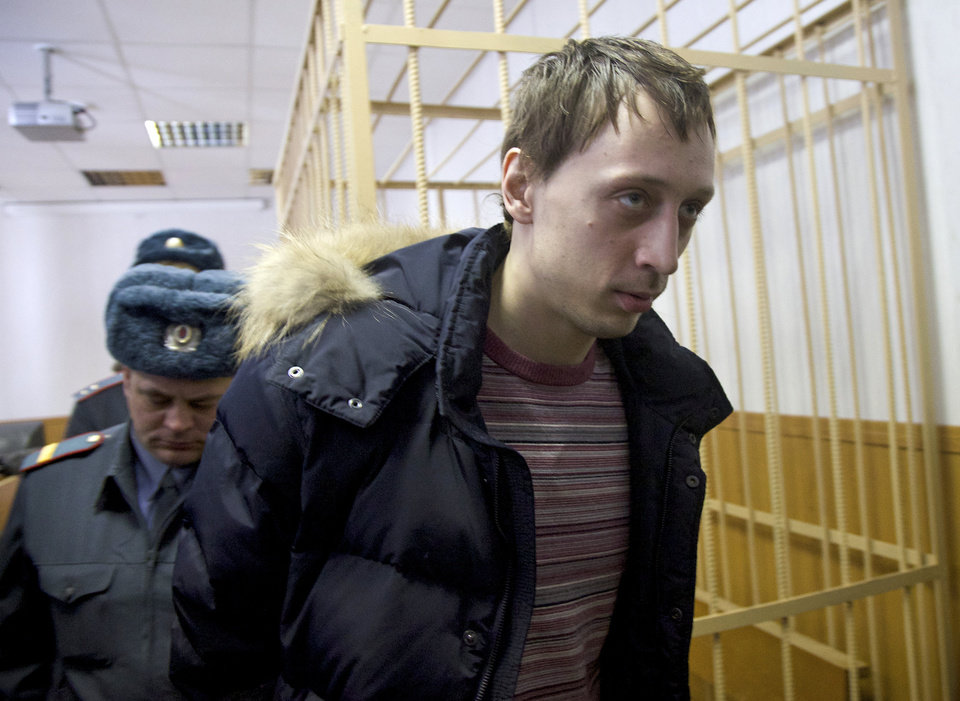 Photo - Pavel Dmitrichenko, foreground, is escorted out of a courtroom in Moscow, Russia, on Thursday, March 7, 2013. The star dancer accused of masterminding the attack on the Bolshoi ballet chief acknowledged Thursday that he gave the go-ahead for the attack, but told a Moscow court that he did not order anyone to throw acid on the artistic director's face. The judge, however, refused to release Bolshoi soloist Pavel Dmitrichenko on bail and ordered him held until at least Apr. 18 while the investigation continued. (AP Photo/Ivan Sekretarev)