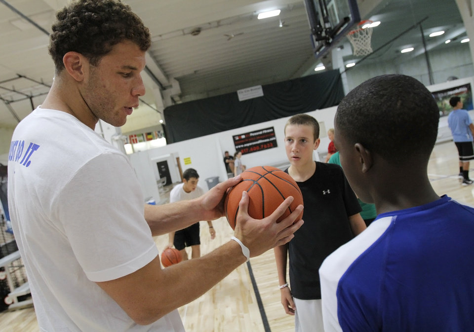 Blake Griffin gives tips to Ben Carllson (center), 13 of Edmond, and Kamren Evans, 13 of Edmond, during the Blake Griffin basketball camp at the Santa Fe Family Life Center in Oklahoma City Thursday, Aug. 4, 2011.  Photo by Garett Fisbeck, The Oklahoman