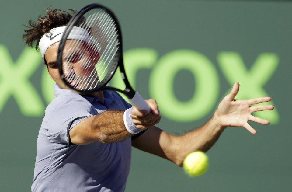 Photo - Roger Federer, of Switzerland, returns the ball to Richard Gasquet, of France, during the Sony Open tennis tournament, Tuesday, March 25, 2014, in Key Biscayne, Fla. (AP Photo/Luis M. Alvarez)