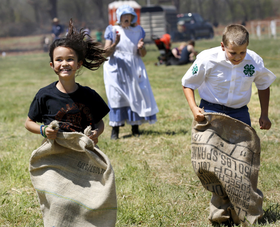 "Photo - Bailey Barrett, 10, of Wellston, left, crosses the finish line for first place in a sack race with two boys. Cheering for them in background is Joyce Stockton. Stockton is with women from Grady County Rural Neighbors, Oklahoma Home and Community Education Group, in Chickasha, who hosted a tent where children could play ""non-electronic"" games typical of ones played by young people in the early 1900s.  Children were able to toss horseshoes, play jacks, jump rope and engage in other assorted fun physical activities.  Oklahoma Cooperative Extension Service celebrated their 100th anniversary with a Whistle Stop and Festival on Saturday, April, 12, 2014 at the Rock 'N Rail yard near Highway 66 in Wellston, Oklahoma.  ""In the early 1900s, trains were the modern way to travel and early Extension agents were allowed to 'ride the rails', going from town to town presenting demonstrations  and showing people how they might improve the quality of their lives by making use of the latest science-proven advances, practices and products,"" said James Trapp. OCES associate director. A train coming into town was sometimes referred to  as a ""county fair on wheels."" As part of its centennial celebration, Extension conducted an historic reenactment  of the type of whistle stop tours that would have occurred   in 1914. Visitors  at the festival were given the opportunity to visit a variety of tents and booths offering demonstrations and hands-on activities representative of Extension programs. Photo by Jim Beckel, The Oklahoman"