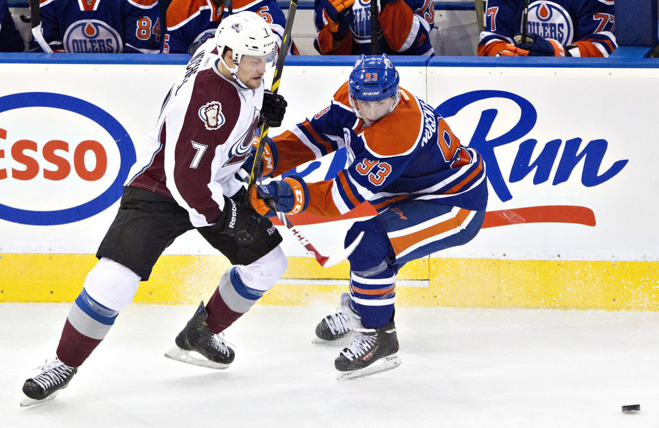 Photo - Colorado Avalanche's John Mitchell (7) is checked by Edmonton Oilers' Ryan Nugent-Hopkins (93) during second period NHL hockey action in Edmonton, Alberta, on Tuesday April 8, 2014. (AP Photo/The Canadian Press, Jason Franson)