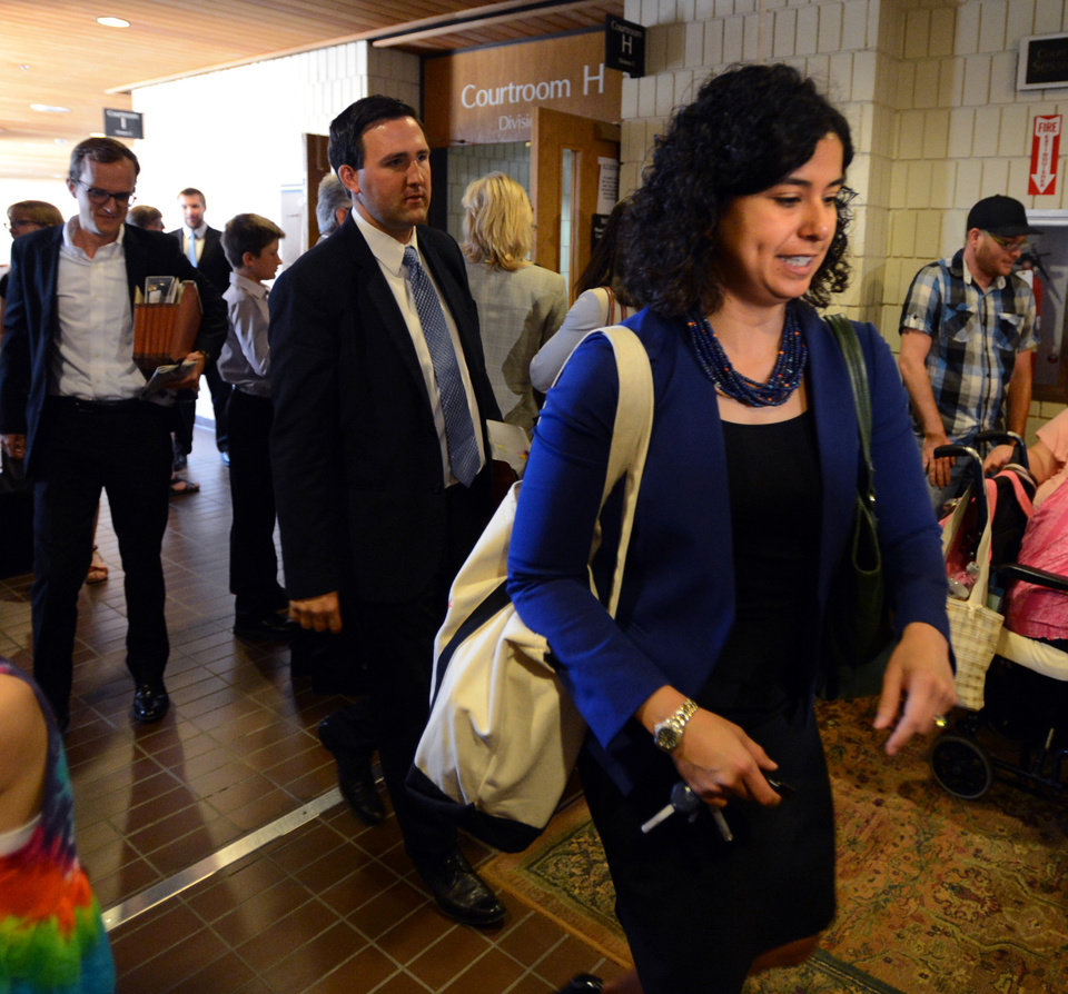Photo - Colorado Assistant Solicitor General Michael Francisco, left, and LeeAnn Morrill, leave the courtroom, Wednesday, July 9, 2014 in Boulder, Colo. Boulder County Clerk and Recorder Hillary Hall is in court to respond to a suit brought by Colorado Attorney General John Suthers who wants the court to issue an injunction to stop the county from issuing marriage licenses to same-sex couples. (AP Photo/Daily Camera, Cliff Grassmick)