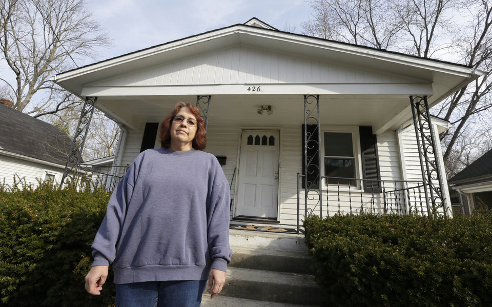 Photo - Regina Bachman stands outside her home that has a small creek running behind it in Loveland, Ohio on Friday, March 21, 2014. Bachman bought the home in September 2013 and was initially told by the bank that flood insurance on the property would be affordable, only to find out after closing that the rates were going to increase over $7,000 more annually with new premiums for the National Flood Insurance Program. (AP Photo/Al Behrman)