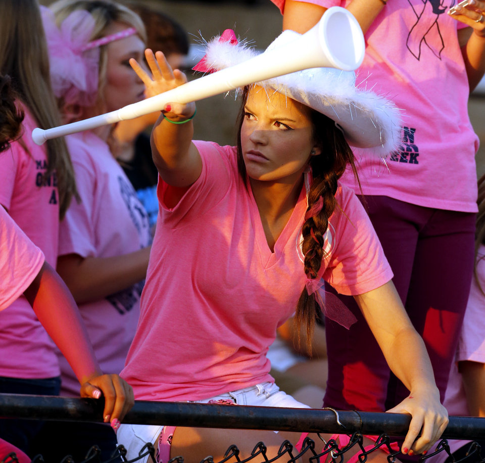 Photo - Southmoore fan Brittani Weems wears cancer awareness pink as the Southmoore Sabercats play the Lawton High School Wolverines in high school football on Friday, Oct. 11, 2013, in Moore, Okla. Photo by Steve Sisney, The Oklahoman