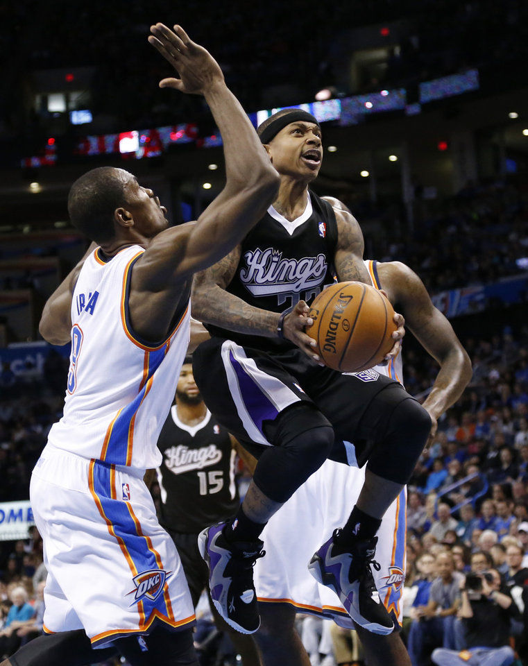 Photo - Sacramento Kings guard Isaiah Thomas (22) drives between Oklahoma City Thunder forward Serge Ibaka (9) and center Kendrick Perkins (5) in the second quarter of an NBA basketball game in Oklahoma City, Sunday, Jan. 19, 2014. (AP Photo/Sue Ogrocki)