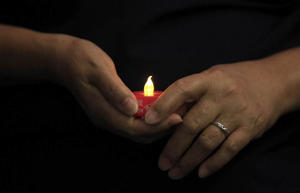 Photo - A woman holds an LED candle as she offers prayers during a mass prayer for the missing Malaysia Airlines Flight 370, in Kuala Lumpur, Malaysia, Sunday, April 6, 2014. The head of the multinational search for the missing Malaysia airlines jet said that electronic pulses reportedly picked up by a Chinese ship are an encouraging sign but stresses they are not yet verified. (AP Photo/Lai Seng Sin)