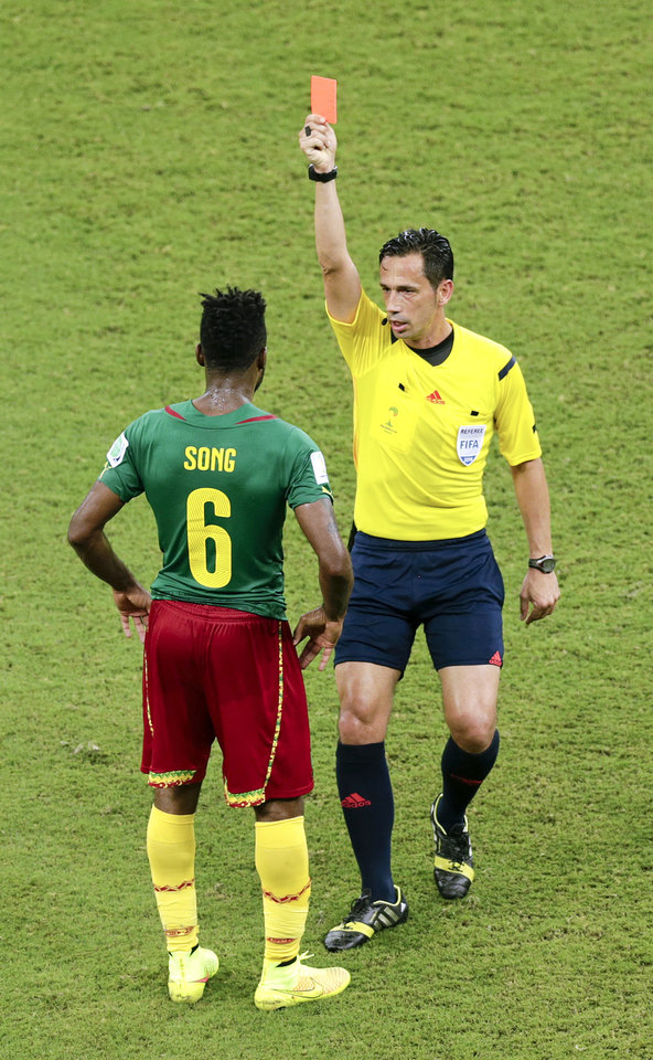 Photo - Referee Pedro Proenca from Portugal gives Cameroon's Alex Song (6) a red card, during the group A World Cup soccer match between Cameroon and Croatia at the Arena da Amazonia in Manaus, Brazil, Wednesday, June 18, 2014. Song intentionally struck an opposing player in the back. (AP Photo/Fernando Llano)