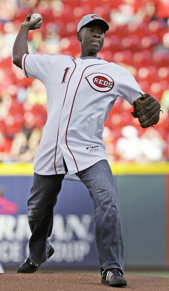 Photo - Actor Don Cheadle throws out a ceremonial first pitch prior to a baseball game between the Cincinnati Reds and the Philadelphia Phillies, Friday, June 6, 2014, in Cincinnati. (AP Photo/Al Behrman)