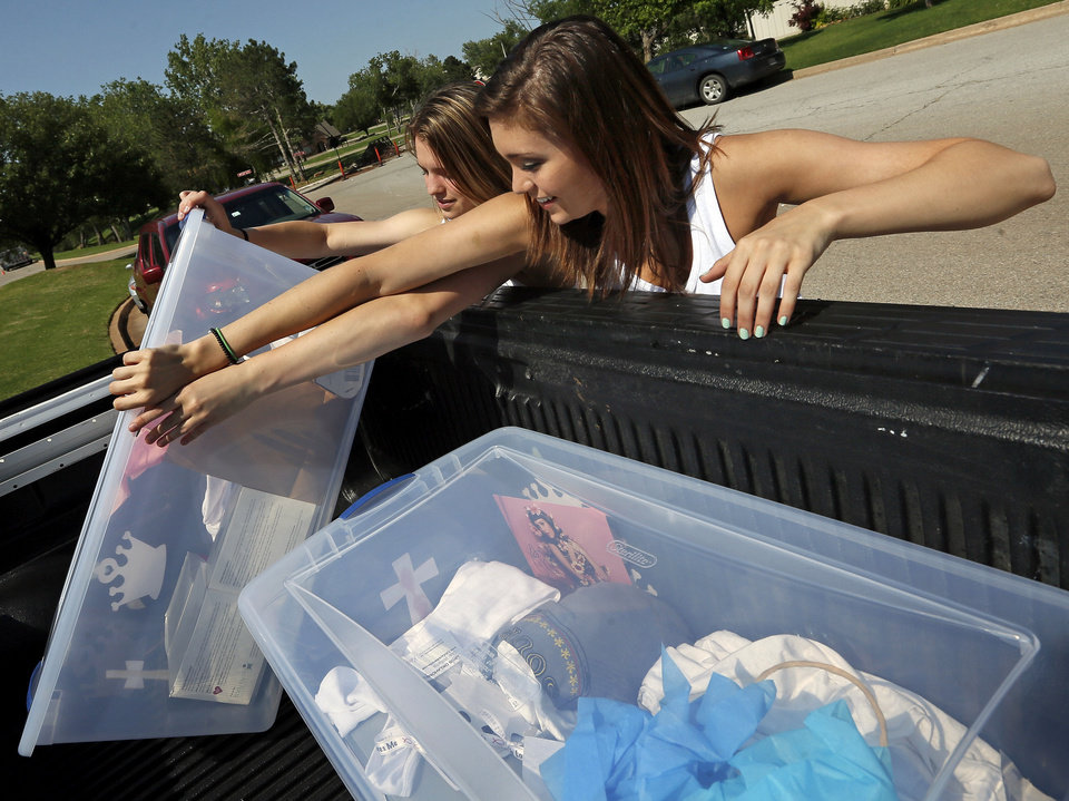 Photo - Ashley Stover, 15, right, and Abby Vinyard, 15, of Moore, Okla., load into a truck their containers of clothes, shoes, autographed pictures and other items they collected during the
