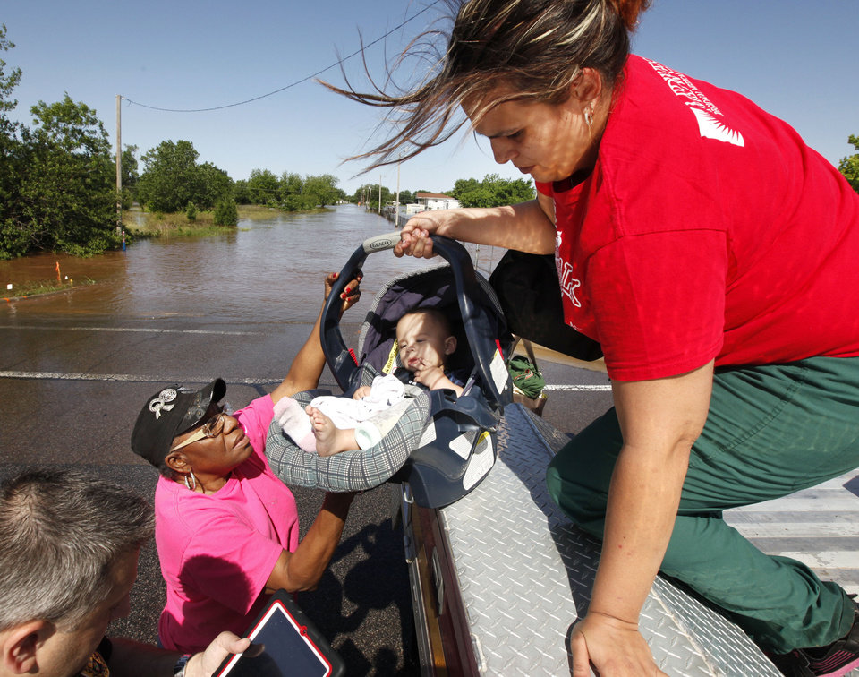 Photo - Riley Webb hands her seven month old baby Bryce Webb down to Oklahoma County Commissioner Willa Johnson after being rescued by Midwest City Fire Dept. personnel from a flooded mobile home park off of Air Depot Blvd. between NE 10th and NE 23rd St. in Midwest City, OK, Saturday, June 1, 2013, after up to eight inches of rain fell during the previous 24 hours. Photo by Paul Hellstern, The Oklahoman