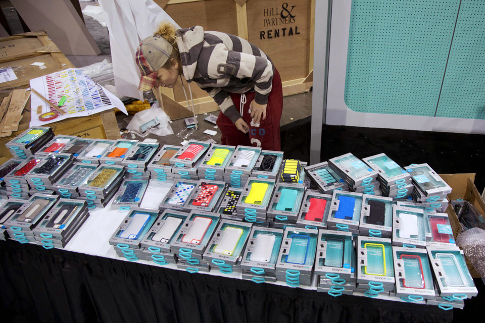 Las Vegas Convention Center exhibit contractor Ruachelle Kulak searches through stacks of cell phone case while setting up a booth for X-Doria, Sunday, Jan. 6, 2013, in Las Vegas. X-Doria, a mobile accessories company, is one of thousands of consumer electronics exhibitors that will be showing products at the International Consumer Electronics Show, which opens on Tuesday and runs through Friday. (AP Photo/Julie Jacobson)