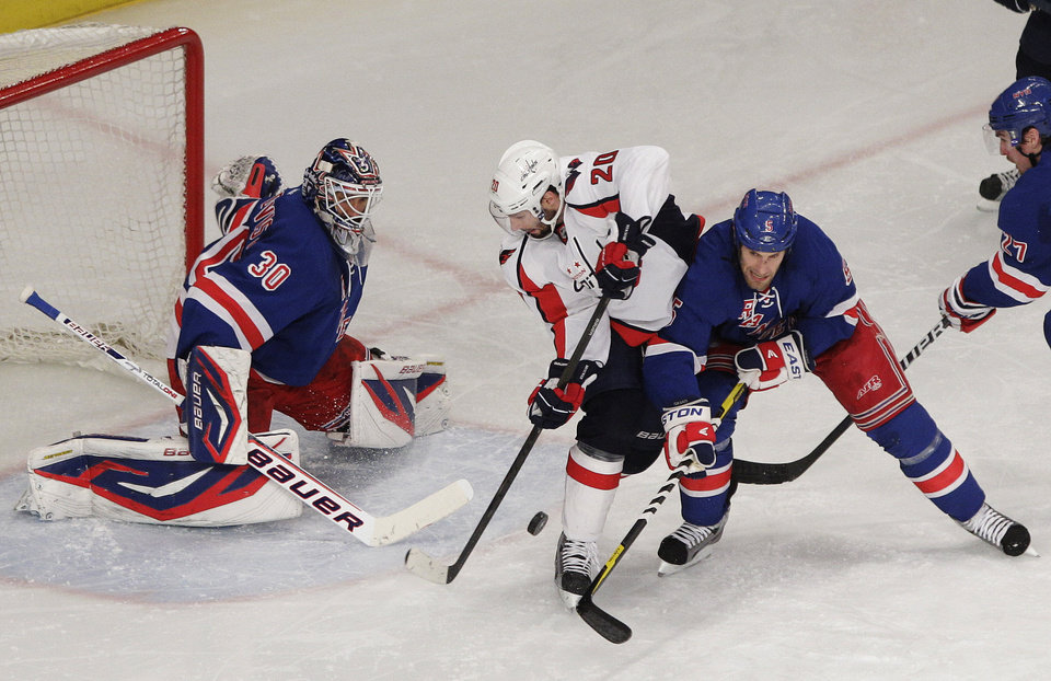 Photo -   Washington Capitals' Troy Brouwer (20) is defended by New York Rangers' Dan Girardi (5) and goalie Henrik Lundqvist (30) during the second period of Game 1 in the second round of the NHL hockey Stanley Cup playoffs Saturday, April 28, 2012, in New York. (AP Photo/Frank Franklin II)