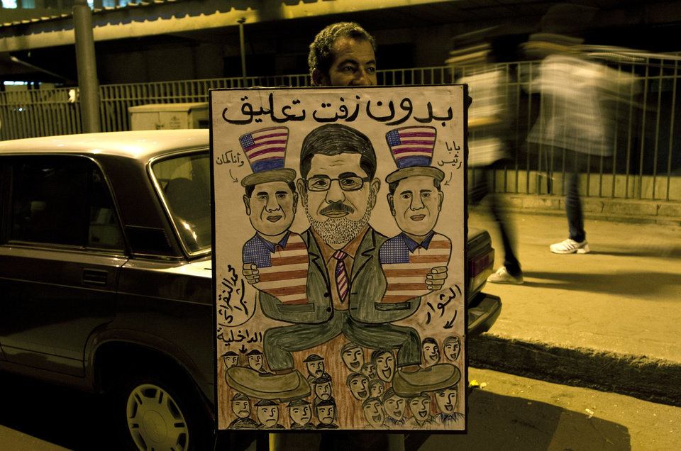 "An Egyptian protester holds a poster depicting Egyptian President Mohammed Morsi, center, holding his two sons, with the colors of the American flag and Arabic writing that reads, ""with no comment,"" during a march marking the first anniversary of 26 Coptic Christians killed during an anti-government demonstration, in front of the National State T.V. building, known as Maspero, in Cairo, Egypt, Tuesday, Oct. 9, 2012. Muslim clerics, Christian priests, activists and former liberal lawmakers were among those marching to mark the anniversary of the ""Maspero massacre,"" referring to the name of the state TV building, where the clashes broke out a year ago. (AP Photo/Khalil Hamra)"
