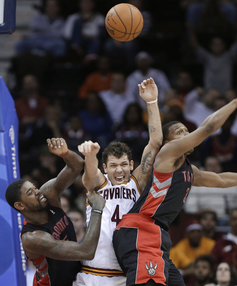 Cleveland Cavaliers' Luke Walton tips the ball away between Toronto Raptors' Amir Johnson (15) and Kyle Lowry (3) during the fourth quarter of an NBA basketball game Wednesday, Feb. 27, 2013, in Cleveland. The Cavaliers won 103-92. (AP Photo/Tony Dejak)