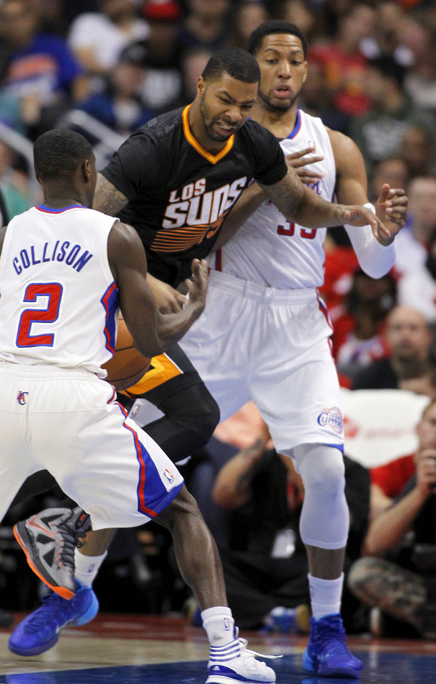 Photo - Los Angeles Clippers guard Darren Collison (2) steals the ball away from Phoenix Suns forward Marcus Morris, center, with Clippers forward Danny Granger, right, during the first half of an NBA basketball game Monday, March 10, 2014, in Los Angeles. (AP Photo/Alex Gallardo)