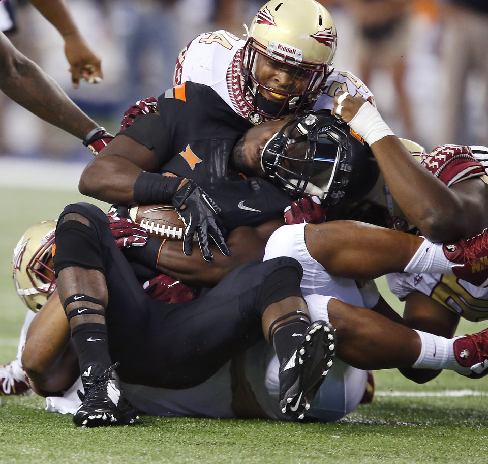 Photo - The Florida State defense stops Oklahoma State's Desmond Roland (26) during the college football game between Oklahoma State University (OSU) and Florida State University (FSU) at the AdvoCare Cowboys Classic at AT&T Stadium in Arlington, Texas on Saturday, Aug. 30, 2014. Photo by Chris Landsberger, The Oklahoman