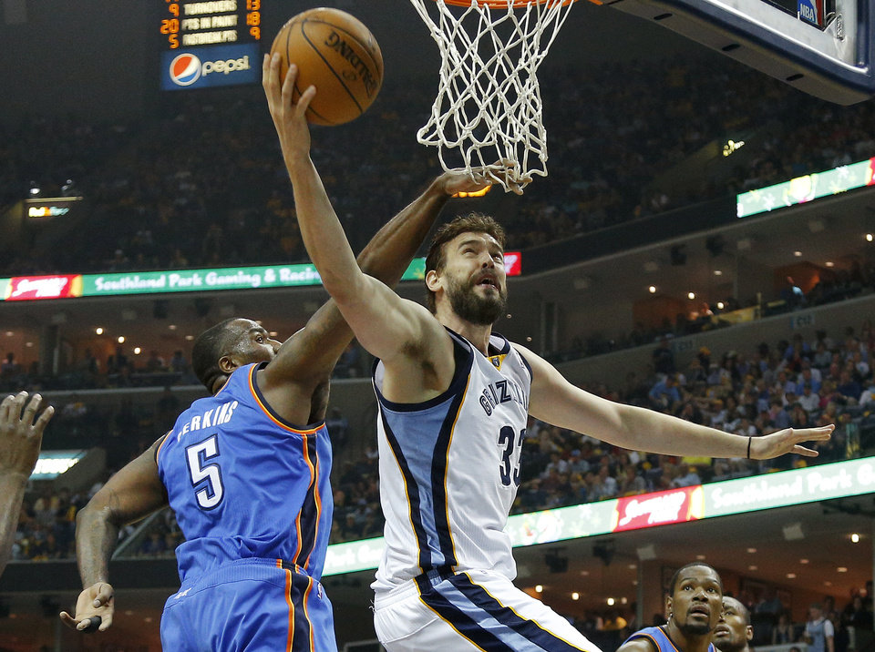 Photo - Memphis' Marc Gasol (33) goes past Oklahoma City's Kendrick Perkins (5) during Game 4 in the first round of the NBA playoffs between the Oklahoma City Thunder and the Memphis Grizzlies at FedExForum in Memphis, Tenn., Saturday, April 26, 2014. Photo by Bryan Terry, The Oklahoman