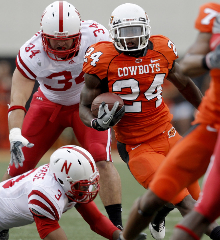OSU's Kendall Hunter runs past Nebraska's Rickey Thenarse, bottom, and Cameron Meredith during the college football game between the Oklahoma State Cowboys (OSU) and the Nebraska Huskers (NU) at Boone Pickens Stadium in Stillwater, Okla., Saturday, Oct. 23, 2010. Photo by Bryan Terry, The Oklahoman