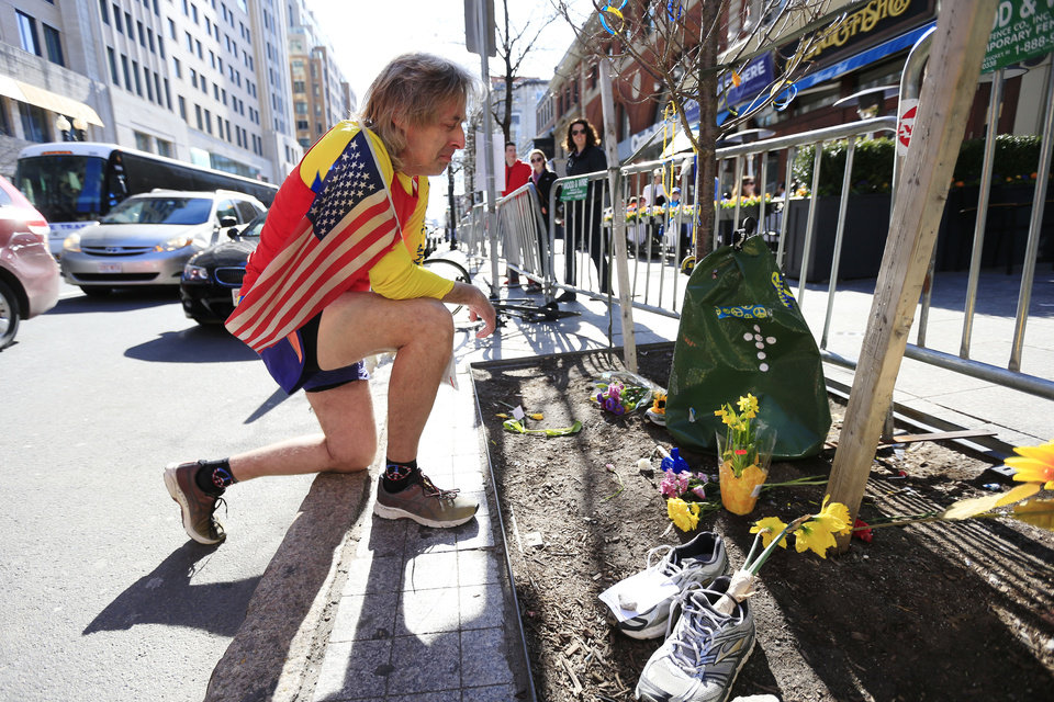 Photo - Ron McCracken of Dallas pays his respects at a makeshift memorial honoring to the victims of the 2013 Boston Marathon bombings ahead of Monday's 118th Boston Marathon, Sunday, April 20, 2014, in Boston. McCracken's race last year was cut short due to bombings and Monday's race will mark his 14th year running in the Boston Marathon.  The memorial is where the second of two explosions happened last year near the finish line.  (AP Photo/Matt Rourke)