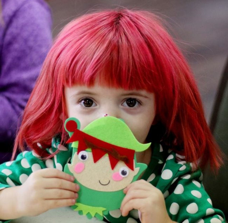 Photo -  Melanie McCracken, 3, shows the ornament she made during the