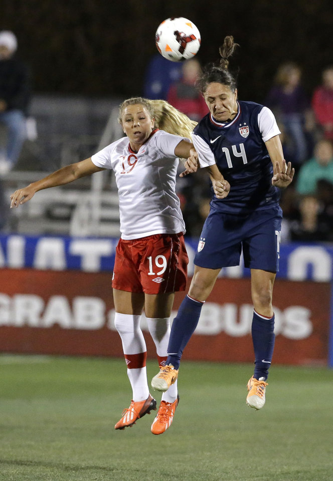 Photo - United States defender Stephanie Cox (14) and Canada forward Adriana Leon (19) jump for a header during the first half of a soccer game on Friday, Jan. 31, 2014, in Frisco, Texas. (AP Photo/LM Otero)
