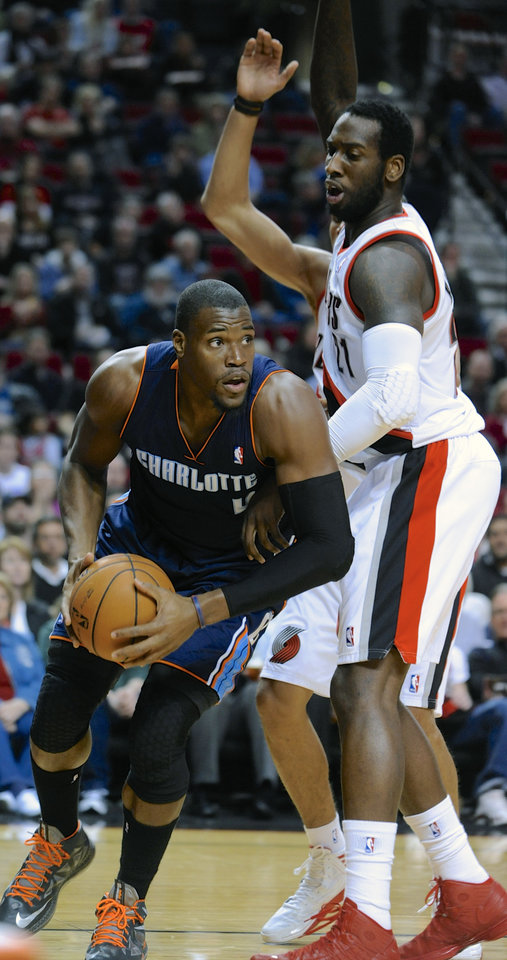 Photo - Charlotte Bobcats' Jeff Adrien (4) looks to pass against Portland Trail Blazers' JJ Hickson (21) during the first half of an NBA  basketball game in Portland, Ore., Monday, March 4, 2013. (AP Photo/Greg Wahl-Stephens)